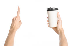 Breakfast and coffee theme: man's hand holding white empty paper coffee cup with a brown plastic cap isolated on a white backgroun. D in the studio, advertising royalty free stock images