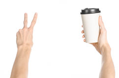 Breakfast and coffee theme: man's hand holding white empty paper coffee cup with a brown plastic cap isolated on a white backgroun. D in the studio, advertising stock image