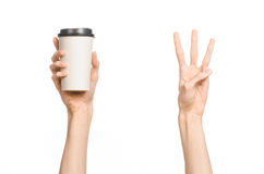 Breakfast and coffee theme: man's hand holding white empty paper coffee cup with a brown plastic cap isolated on a white backgroun. D in the studio stock photos
