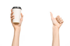 Breakfast and coffee theme: man's hand holding white empty paper coffee cup with a brown plastic cap isolated on a white backgroun. D in the studio stock images