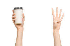 Breakfast and coffee theme: man's hand holding white empty paper coffee cup with a brown plastic cap isolated on a white backgroun. D in the studio royalty free stock photo