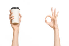 Breakfast and coffee theme: man's hand holding white empty paper coffee cup with a brown plastic cap isolated on a white backgroun. D in the studio stock image