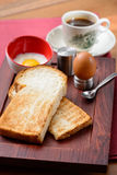 Breakfast with coffee, toast bread and half-boiled egg Stock Image