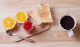 Breakfast with Coffee, toasts, oranges and strawberry jam on wooden table Stock Photography