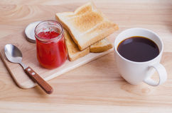 Breakfast with Coffee, toasts and strawberry jam on wooden table Stock Images
