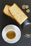 Breakfast. A coffee, two slices of pound cake and a glass of water. Some coins in the corner royalty free stock photos