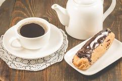 /breakfast com copo, bule e eclairs de café em uma tabela/café da manhã de madeira com copo, bule e eclairs de café em uma tabela fotos de stock royalty free