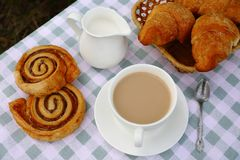 A cup of tea with cream and bakery stock image