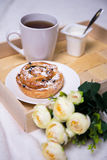 Breakfast concept - close up of wooden tray with bun, tea, yoghu Royalty Free Stock Photos