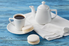 Breakfast concept. Coffee cup and white macaroon on napkin royalty free stock photo