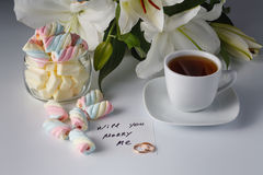 Breakfast concept. Cup of tea, white lily, colored marshmallow Royalty Free Stock Images