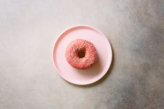 Breakfast concept. Donut on pink plate over concrete background with copy space. Top view, flat lay stock photography