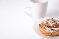 Breakfast concept - sweet bun with raisins and cup of coffee or Stock Photo