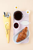 Breakfast consisting of black coffee, milk and a croissant with Stock Images