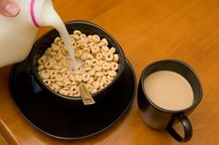 Breakfast consisting of cereal with milk and coffee with cream Stock Image