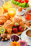 Breakfast consisting of croissants, coffee, fruits, orange juice Stock Images