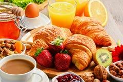 Breakfast consisting of croissants, coffee, fruits, orange juice Royalty Free Stock Photo