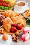 Breakfast consisting of croissants, coffee, fruits, orange juice Stock Photo
