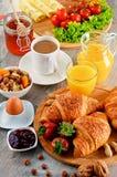 Breakfast consisting of croissants, coffee, fruits, orange juice Stock Photos