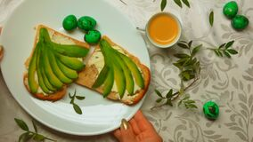 Breakfast consisting of espresso, an avocado sandwich and green Easter eggs. Easter breakfast consisting of espresso coffee, an avocado sandwich and green Easter stock video