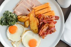 Delicious on the morning. Breakfast consists of eggs, bacon, sausage, bacon, potato and spinach with cheese. Breakfast consists of eggs, bacon, sausage, bacon stock images