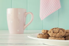 Breakfast: cookies and milk. Some chocolate chip cookies on a plate and a pink mug on a white wooden table with a robin egg blue background and a pink checkered Royalty Free Stock Photography