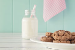 Breakfast: cookies and milk. Some chocolate chip cookies on a plate and a school milk bottle with a straw on a white wooden table with a robin egg blue Royalty Free Stock Photography