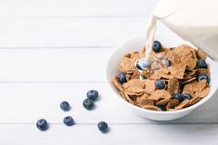 Breakfast with corn flakes with fresh berries and pouring milk on white wooden background. Selective focus and shallow depth of fi Royalty Free Stock Images