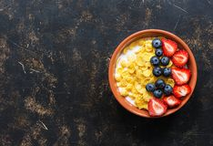 Breakfast corn flakes with milk and fresh berries, strawberries, blueberries on a dark background. Top view, copy space. Dietary f royalty free stock photo