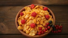Breakfast of cornflakes with berries in bowl stock video
