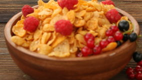 Breakfast of cornflakes with berries in bowl stock video footage