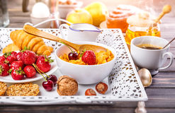 Breakfast with cornflakes berry honey and croissant. On wooden board white tray Stock Photos