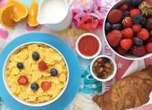 Breakfast with cornflakes, milk, croissants, jam, fresh fruits and almonds. Healthy breakfast. Cornflakes, milk, fresh fruits as blueberries, strawberries and Royalty Free Stock Image