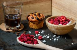 Breakfast of cottage cheese with raspberries, coffee and blueberry muffin. Cottage cheese with raspberries, coffee in a cup and blueberry muffin for breakfast Royalty Free Stock Images