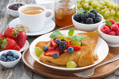 Breakfast - crepes with fresh berries and honey, coffee, closeup Royalty Free Stock Image