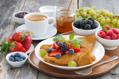 Breakfast - crepes with fresh berries and honey, coffee Royalty Free Stock Image