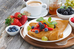 Breakfast - crepes with fresh berries and honey, coffee. On wooden background, close-up stock image