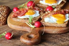 Breakfast of crispy bacon, fried eggs and bread. Sandwiches on cutting board. Rustic table Royalty Free Stock Photo