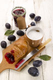 Breakfast with croissant and cafe au lait. Breakfast with croissant, plum jam and cafe au lait Stock Photo