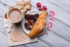 Breakfast, a croissant with a chocolate cake, on a gray background, a number of pink petals, a free place for text. Royalty Free Stock Photos