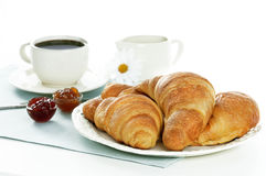 Breakfast with croissant and coffee. Croissants,marmelades and coffee on a light blue table cloth stock image