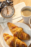 Breakfast Croissant, Coffee and Alarm Clock. A continental breakfast of croissant pastries and coffee Illuminated with golden early morning sunshine and Royalty Free Stock Photo