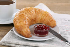 Breakfast with croissant, coffee and newspaper Stock Photos