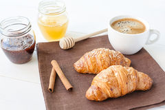 Breakfast with croissant and cup of coffee. On the tableclothes Royalty Free Stock Photo