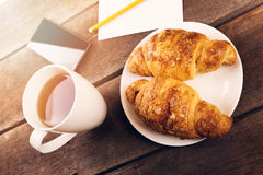 breakfast croissant with cup of tea on wooden table Stock Image