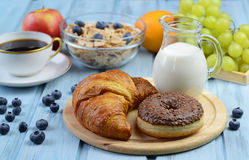 Breakfast with croissant, donut, coffee, cereal and fruits Stock Photo