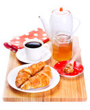 Breakfast with croissant, honey and coffee on wooden board Stock Photography