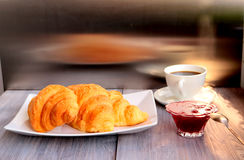 Breakfast - croissant, jam and coffee - served on a wooden table. Royalty Free Stock Photos