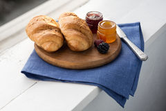 Breakfast with croissant. A light breakfast consisting of croissants with jam and orange juice over white over wooden background. Shallow DOF. Focus on the jars royalty free stock photo