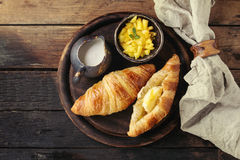 Breakfast with croissant and mango fruit. Breakfast with two croissant, butter, cream and sliced mango fruit, served on wood round serving board with textile Stock Photos